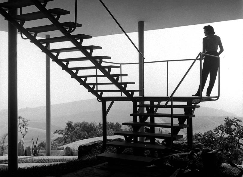 Biografia de Lina Bo Bardi. Na foto, na escada da Casa de Vidro.