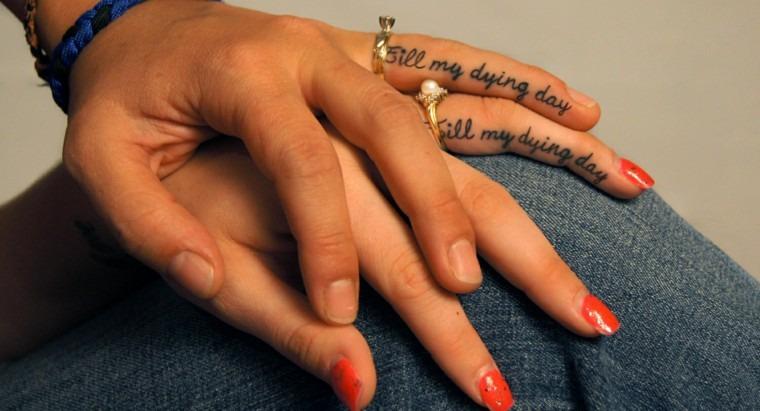 Tatuagem de casal com frase no dedo e alianças.